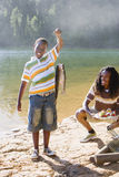 Proud boy (8-10) holding aloft fish on lakeside camping trip, father holding plate of food, smiling, portrait Royalty Free Stock Photography