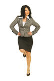 Proud business woman equilibrium. Proud business woman standing in on leg with hands on waist and having a good equilibrium isolated on white background Royalty Free Stock Image