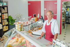 Proud butcher stood by display. Proud butcher stood by his display Stock Images