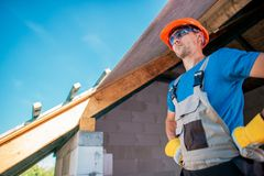Proud Caucasian Home Builder. Contractor Preparing For Roof Finishing. House Building Concept royalty free stock photography