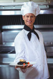Proud chef holding a plate of squid ink spaghetti Stock Photos