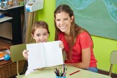 Proud child showing drawing. In kindergarten with nursery teacher stock photo