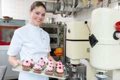 Proud confectioner showing muffins she baked. Proud confectioner or Patissier showing muffins she baked Royalty Free Stock Photo