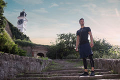 Proud confident athlete man standing posing sunny day sport clot. Hes stairs old fortress Royalty Free Stock Images