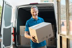 Delivery man holding parcel. Proud delivery man in blue uniform holding parcel and looking at camera. Smiling mature courier standing in front of cargo van Royalty Free Stock Images