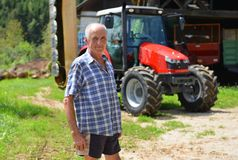 Proud farmer standing in front of his tractor Royalty Free Stock Image