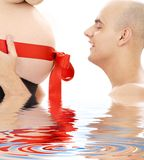 Proud father and belly with red ribbon in water Stock Images