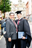 Proud father happy son. A young graduating posing with his father on his graduation day Stock Photography