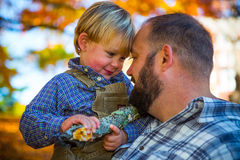Proud father holding blonde boy in fall Stock Photos