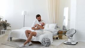Proud father holding his newborn baby daughter in his at home.  stock video