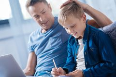 Proud father patting son on the head while he studying Stock Image
