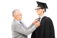 Proud father preparing his son for graduation. Isolated on white background stock images