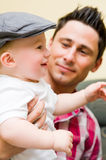 Proud father with son. Proud father holding his baby son wearing a hat royalty free stock photos
