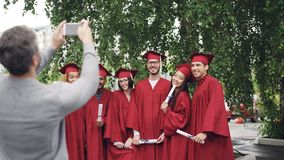 Proud father is taking pictures of graduating students with smartphone while young people are posing, waving hands with. Proud father is taking pictures of merry stock footage