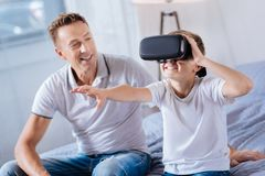 Proud father watching his happy boy test VR headset Stock Photo