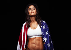 Proud female athlete wrapped in American Flag. Portrait of proud female athlete wrapped in American Flag against black background. Muscular young woman looking Royalty Free Stock Photos