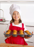 Proud female child presenting her self made muffin cakes learning baking wearing red apron and cook hat smiling happy Royalty Free Stock Image