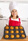 Proud female child presenting her self made muffin cakes learning baking wearing red apron and cook hat smiling happy. Proud female child 4 or 5 years old Royalty Free Stock Photography
