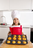 Proud female child presenting her self made muffin cakes learning baking wearing red apron and cook hat smiling happy Stock Photo