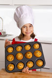 Proud female child presenting her self made muffin cakes learning baking wearing red apron and cook hat smiling happy Stock Images