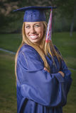Proud Female Graduate Wearing Cap and Gown Outdoors Stock Images