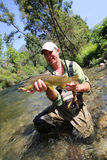 Proud fisherman with big brown trout Stock Photo