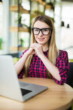 Proud freelance woman with laptop at desk at office and looking at you Royalty Free Stock Image