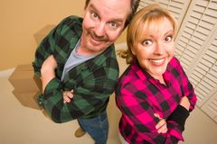 Proud Goofy Couple and Moving Boxes in Empty Room Royalty Free Stock Photography