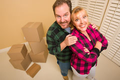 Proud Goofy Couple and Moving Boxes in Empty Room Stock Images