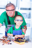 Proud grandfather with grandchild in workshop Royalty Free Stock Image