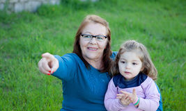 Proud grandmother with her granddaughter sitting on the grass Stock Photography