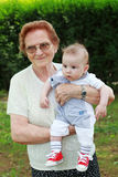 Proud great grandmother. Happy great grandmother holding adorable baby stock photography