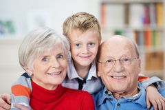 Proud happy grandparents and grandson. Proud happy elderly grandparents posing with their adorable little grandson hugging them from behind grinning playfully at Royalty Free Stock Photos