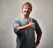 Proud happy man. Smiling proud man with thumb success over gray background royalty free stock image