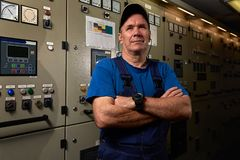 Proud and happy mechanic / chief engineer, posing with his arms crossed in the engine room of an industrial cargo ship royalty free stock images
