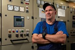 Proud and happy mechanic / chief engineer, posing with his arms crossed in the engine room of an industrial cargo ship royalty free stock photo