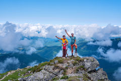 Proud and happy travelers on top of the mountain. Two men and a boy stand over the clouds and rejoice at the achievement of the goal Stock Photo
