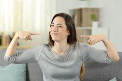 Proud happy woman pointing herself at home. Front view portrait of a proud woman pointing herself sitting on a couch in the living room at home Stock Images