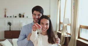 Proud happy young couple holding keys standing in new apartment