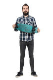 Proud hipster holding long board looking at camera. Royalty Free Stock Photography