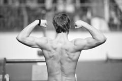 Proud of his shape. Man athlete training outdoor shows his muscular back. Athletic man posing with muscles. Athlete. Muscular back takes break during exhausting royalty free stock photography