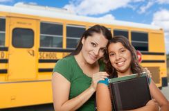 Proud Hispanic Mother and Daughter Near School Bus. Proud Hispanic Mother and Daughter Next to a School Bus royalty free stock image