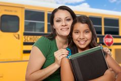 Hispanic Mother and Daughter Near School Bus. Proud Hispanic Mother and Daughter Next to a School Bus royalty free stock photography