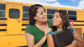 Hispanic Mother and Daughter Near School Bus. Proud Hispanic Mother and Daughter Next to a School Bus stock images