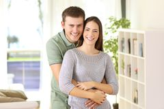 Proud homeowners posing looking at you at home. Portrait of a proud homeowners posing looking at you standing in the living room at home Stock Photography