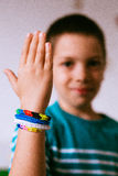 Proud kid showing friendship bracelets Stock Photos