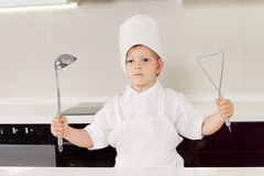Proud little boy chef holding up his utensils Stock Images