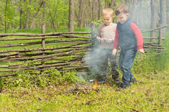 Proud little boys standing watching a burning fire Royalty Free Stock Photography