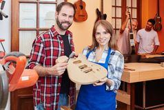 Proud luithier and guitar maker apprentice. Hold guitar in construction stock image