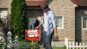 Proud man changing for sale to sold signboard in front of house, buy new home. Stock footage stock video